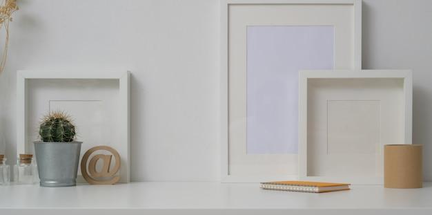 Espacio de trabajo mínimo con marcos simulados y decoraciones en el fondo de la pared blanca