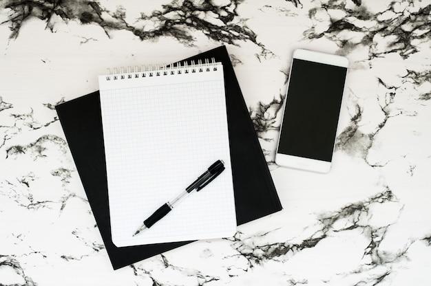 Espacio de trabajo mínimo con notebook y teléfono inteligente sobre un elegante fondo de mármol
