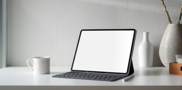 Espacio de trabajo mínimo con tableta digital de pantalla en blanco y espacio de copia