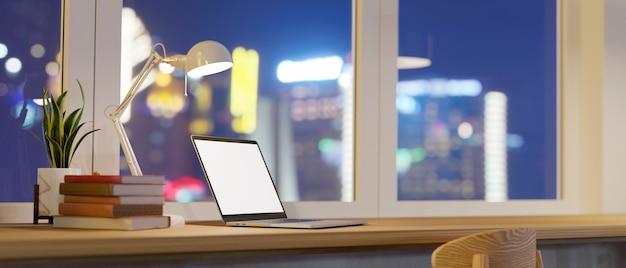 Espacio de trabajo moderno en apartamento con vista nocturna a la ciudad, maqueta de pantalla en blanco para computadora portátil, lámpara de mesa, libros, plantas de interior, espacio en el escritorio de madera, representación 3d, ilustración 3d