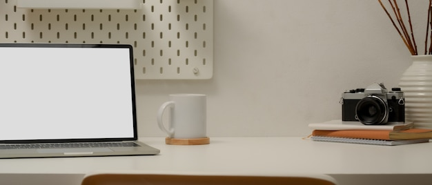 Espacio de trabajo moderno con computadora portátil simulada, taza de café, cámara, libros de horarios, decoraciones
