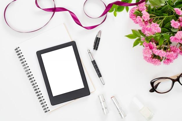 Espacio de trabajo moderno del escritorio de la oficina en el hogar con un libro electrónico de tableta en pantalla en blanco, accesorios femeninos, gafas, cuaderno de papel, ramo de flores rosas rosadas