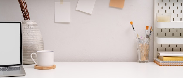 Espacio de trabajo moderno con espacio de copia, maqueta portátil, taza de café, herramientas de pintura y decoraciones.