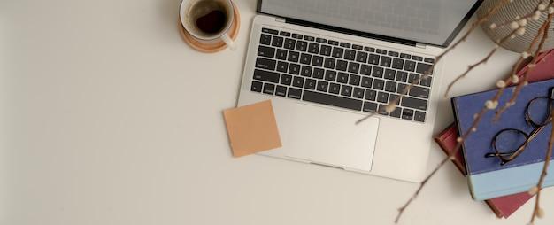 Espacio de trabajo moderno con maqueta portátil, libros de horarios, vasos, taza de café y espacio de copia en mesa blanca