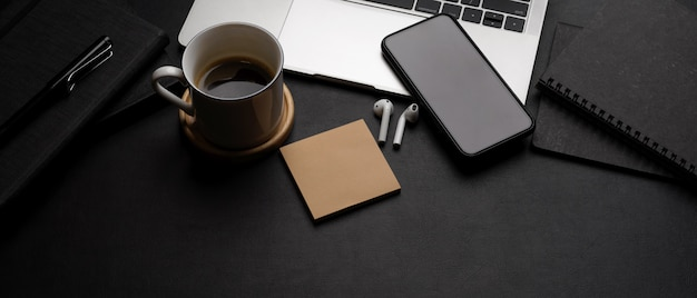 Espacio de trabajo moderno y oscuro con computadora portátil, teléfono inteligente, taza de café, auriculares, bloc de notas y espacio de copia