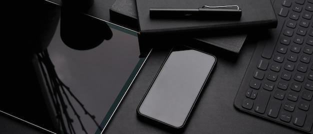 Espacio de trabajo moderno y oscuro con tableta digital, teléfono inteligente, teclado inalámbrico, agendas y bolígrafo