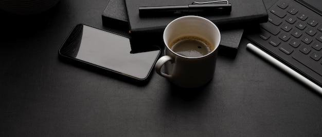 Espacio de trabajo moderno y oscuro con teclado de tableta, teléfono inteligente, taza de café, libros de horarios y espacio de copia