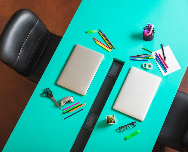 Espacio de trabajo moderno con papelería colorida y portátil cerrado.