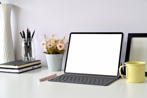 Espacio de trabajo moderno con tableta de pantalla en blanco maqueta