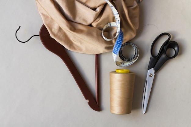 Espacio de trabajo de modista con herramientas y colgador.