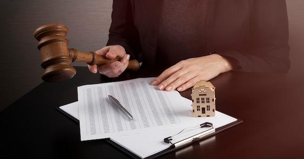 Espacio de trabajo de mujer abogada con martillo de ley, con documento y casa de madera
