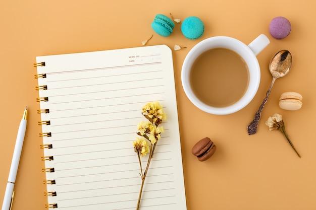 Espacio de trabajo de mujer con macarrones, flores, cuaderno y taza de café.