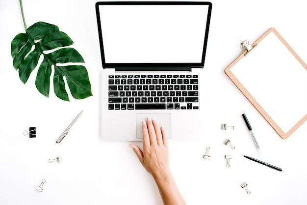 Espacio de trabajo con mujer que trabaja en la computadora portátil con pantalla en blanco