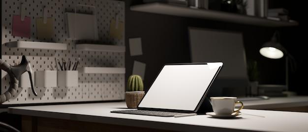 Espacio de trabajo en la noche tableta pantalla vacía en la decoración de la mesa blanca con oficina de papelería en la noche