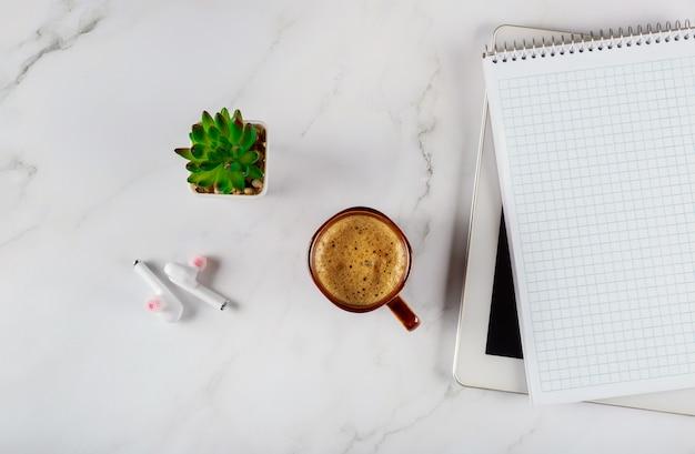 Espacio de trabajo con notebook con auriculares inalámbricos y café en una tableta digital, escritorio de oficina