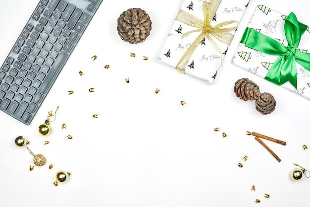 Espacio de trabajo de oficina brillante con regalos de navidad, decoraciones de navidad sobre fondo blanco.