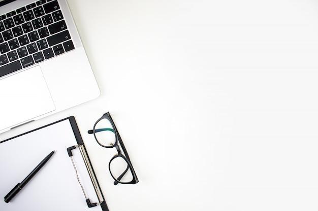 Espacio de trabajo de oficina en casa con laptop, gafas de lectura, portapapeles y accesorios sobre un fondo blanco. lay flat, vista superior copia espacio.