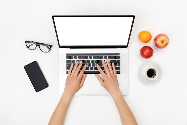 Espacio de trabajo de la oficina en casa. portátil con pantalla en blanco, manos y accesorios en blanco