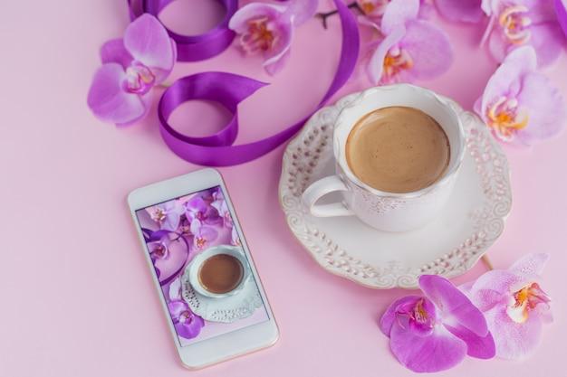 Espacio de trabajo de oficina en casa rosa con teléfono y taza de café. plano de redes sociales con café, flores y teléfono inteligente.