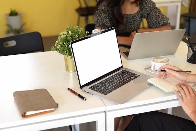 Espacio de trabajo en la oficina dos empleadas están trabajando en una maqueta de pantalla de computadora portátil