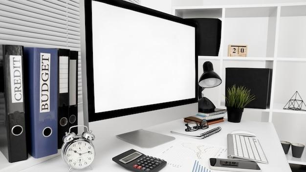 Espacio de trabajo de oficina con pantalla de computadora y lámpara
