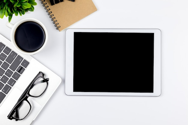 El espacio de trabajo en la oficina con la tableta y con las pantallas en blanco vacías se encuentra en la parte superior, la vista superior con espacio de copia.