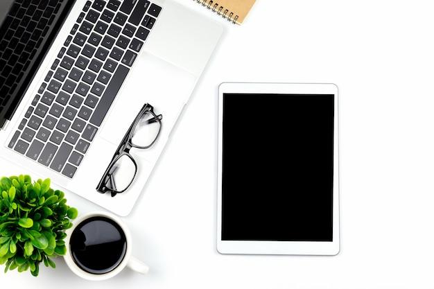 Espacio de trabajo en la oficina con tableta y con pantallas vacías en blanco.