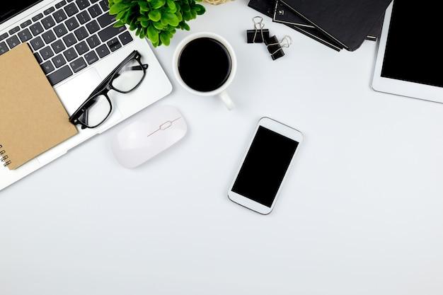 El espacio de trabajo en la oficina con tableta y teléfono inteligente con pantallas vacías en blanco se encuentra en la parte superior, vista superior con espacio para copiar.
