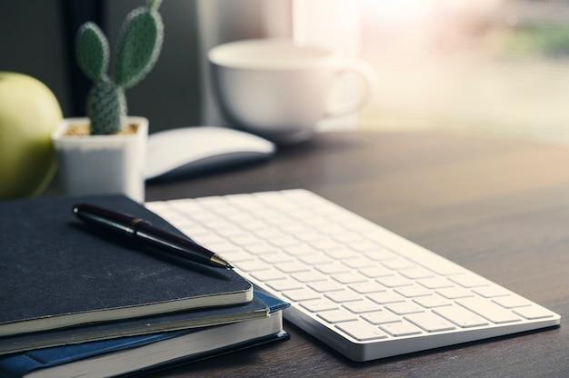 Espacio de trabajo de oficina con teclado de computadora y suministros sobre mesa de madera clara.
