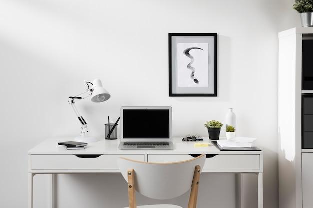 Espacio de trabajo ordenado y ordenado con silla y lámpara.