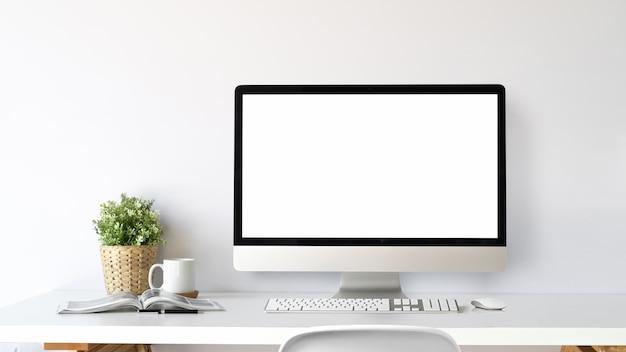Espacio de trabajo con ordenador de pantalla en blanco sobre una mesa blanca