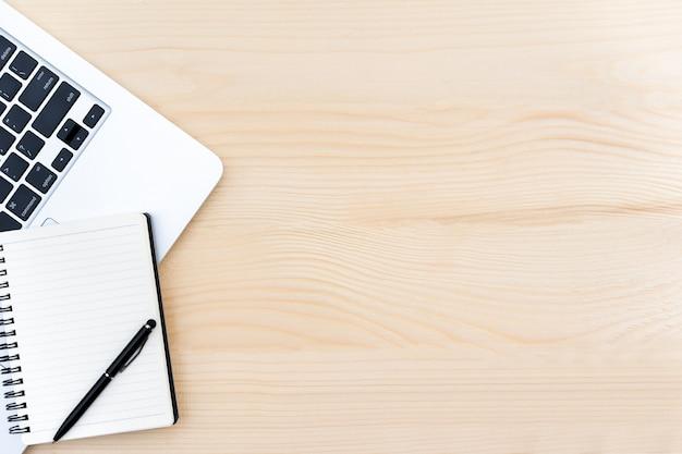 Espacio de trabajo con ordenador portátil y cuaderno sobre la madera de pino.