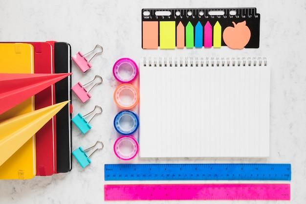 Espacio de trabajo organizado con cuaderno en blanco y suministros de oficina a su alrededor.