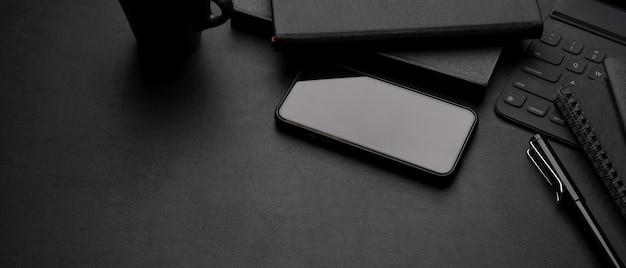 Espacio de trabajo oscuro de lujo con teléfono inteligente, taza, suministros de oficina y espacio de copia