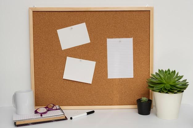 Espacio de trabajo con panel de corcho, plantas, vidrios y útiles de oficina.
