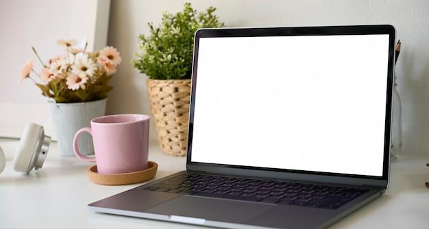 Espacio de trabajo con pantalla blanca aislada maqueta portátil en el escritorio