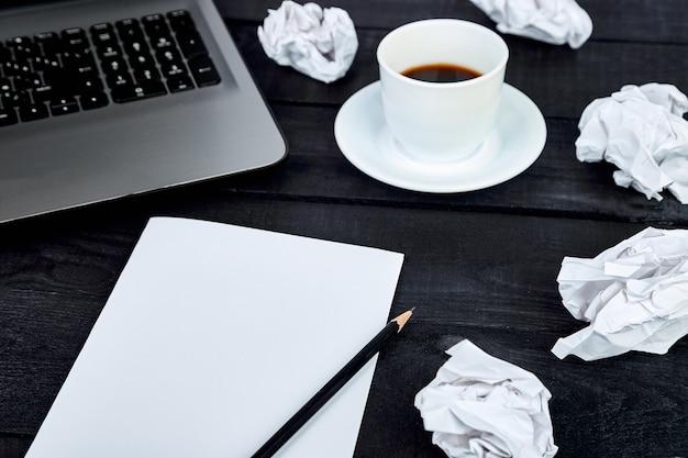 Espacio de trabajo con papel, lápiz, computadora portátil y taza de café.