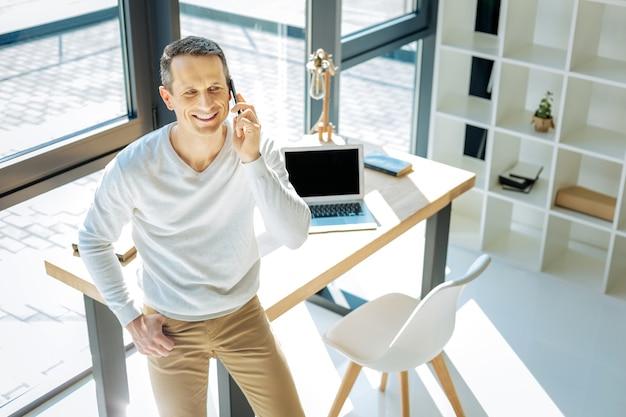 Espacio de trabajo personal. feliz hombre ambicioso positivo sentado en la esquina de la mesa y sonriendo mientras habla por teléfono