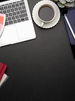 Espacio de trabajo plano creativo con computadora portátil, cuadernos, taza de café, suministros y espacio para copiar, vista superior