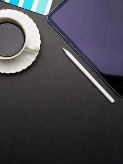 Espacio de trabajo plano creativo con tableta digital, lápiz óptico, taza de café y espacio para copiar en el escritorio negro