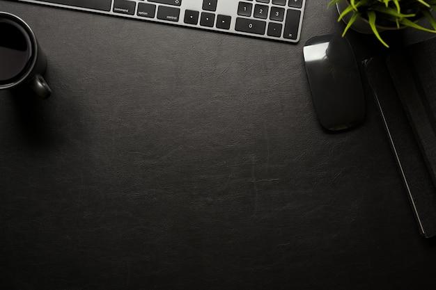Espacio de trabajo plano creativo con taza de mouse de teclado de computadora y espacio de copia en la vista superior de la mesa negra