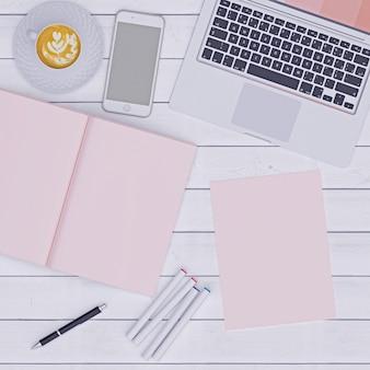 Espacio de trabajo rosa con café de papel de cuaderno y teléfono, plano.