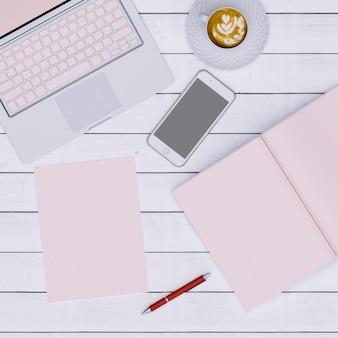 Espacio de trabajo rosa con café de papel de cuaderno y teléfono, vista superior