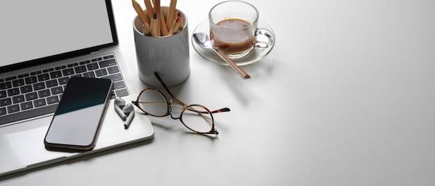 Espacio de trabajo simple con espacio de copia, maqueta portátil, taza de café, papelería, teléfono inteligente y anteojos