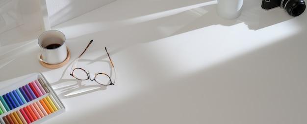 Espacio de trabajo simple con vasos, pasteles al óleo, taza de café, cámara y espacio de copia en mesa blanca