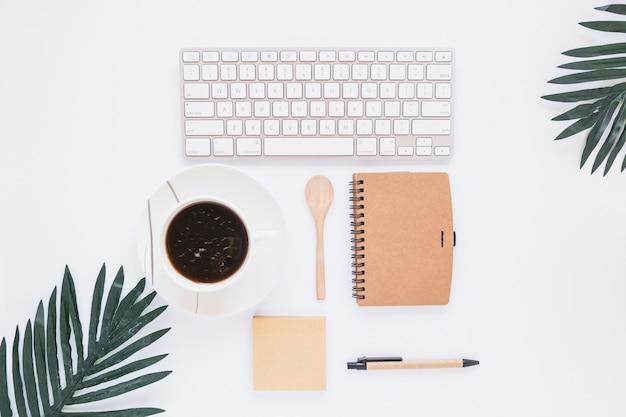 Espacio de trabajo con taza de teclado y estacionario