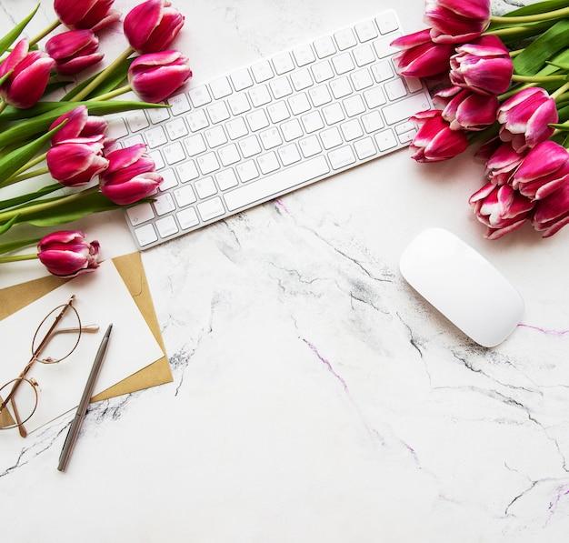 Espacio de trabajo con teclado y tulipanes.