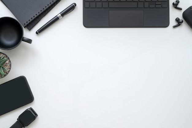 Espacio de trabajo de vista superior en blanco y negro, plano del espacio de trabajo con teclado de computadora negro, teléfono inteligente y suministros en la mesa blanca.