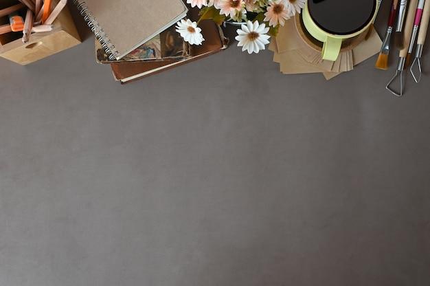El espacio de trabajo de la vista superior del trabajo de escritorio reserva el café, decoración de la flor en espacio de la copia del escritorio de oficina.