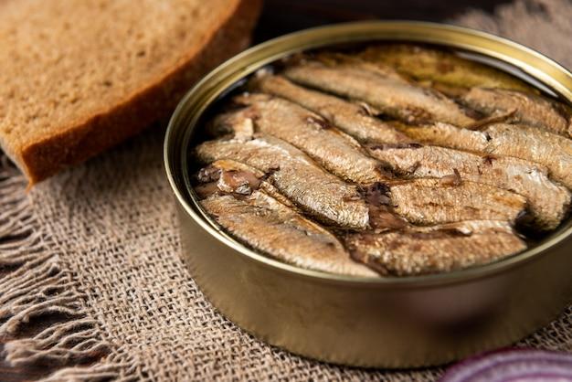 Espadines en una lata y pan sobre mesa de madera